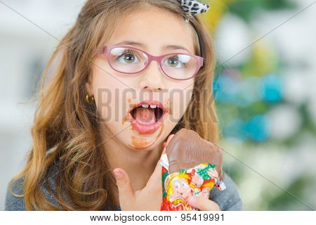 Little girl eating chocolate at Christmas