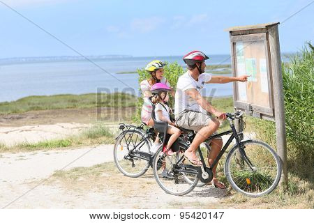 Family of three on a biking day looking at map