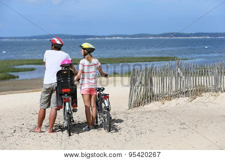 Family on a biking journey making a stop on the beach