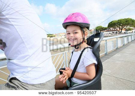 Smiling little girl sitting in child seat on bicycle