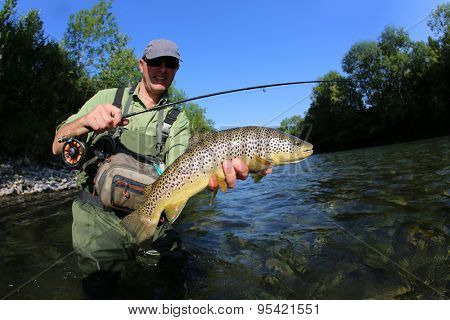 Fisherman holding recently caught brown truit