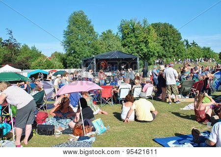 TENTERDEN, ENGLAND - JULY 4, 2015: The audience sit on the grass during the annual free Tentertainment music festival. The community event was first held in 2008.