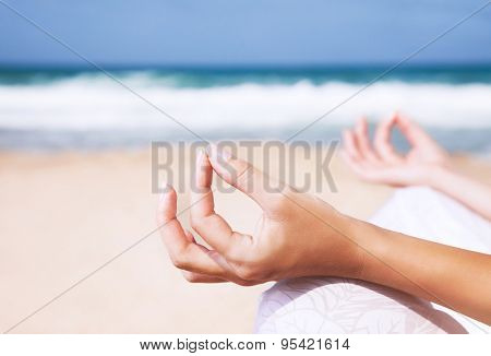 Woman sitting on the beach in lotus pose and meditating, body part, doing yoga exercise outdoors, zen balance and relaxation concept