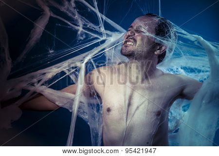 Horror, naked man trapped in a huge spider web