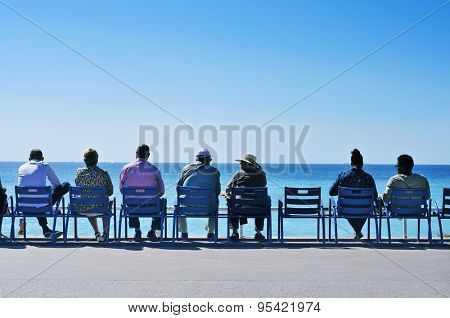 NICE, FRANCE - MAY 16: People sitting in the characteristic blue chairs facing the Mediterranean sea at the Promenade des Anglais on May 16, 2015 in Nice, France