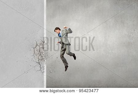 Businessman breaking stone wall with karate punch