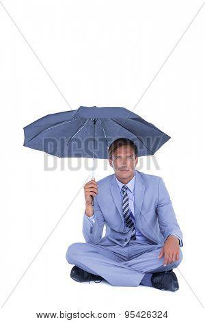 Businessman sheltering under umbrella on white background