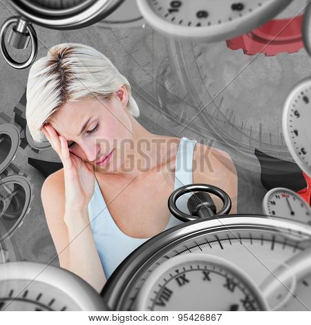 Depressed blonde woman with hand on temple against grey background