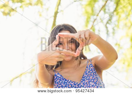 Pretty brunette doing frame with her fingers on a sunny day