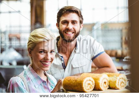Portrait of cute couple on a date looking at the camera at the bakery