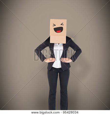 Businesswoman with box over head against grey background with vignette