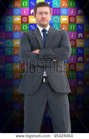 Frowning businessman looking at camera against app wall