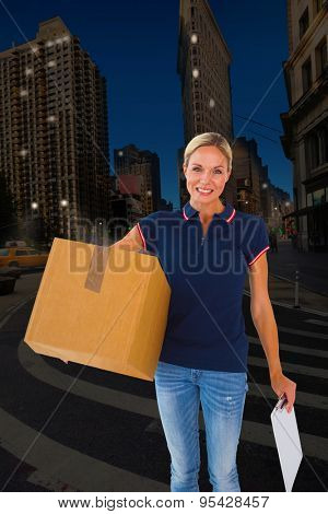 Happy delivery woman holding cardboard box and clipboard against city at night