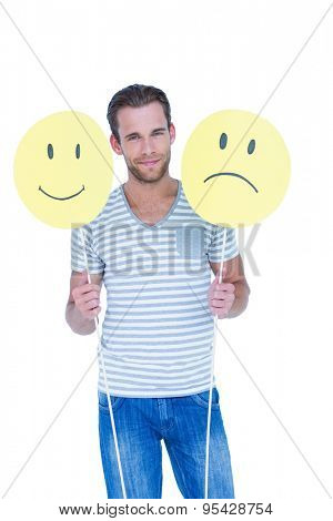 Handsome man holding smiley faces on white background