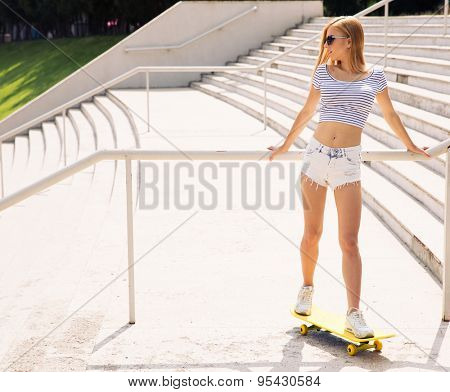 Full length portrait of a beautiful female skater looking away outdoors