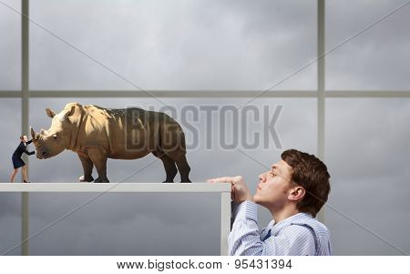 Young man looking from under table on woman fighting with massive rhino