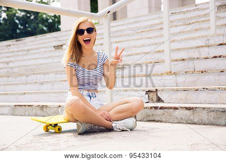 Cheerful female skater showing two fingers sign outdoors