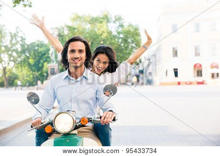 Cheerful couple riding on a scooter in town