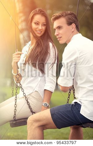 Love couple on swings at park