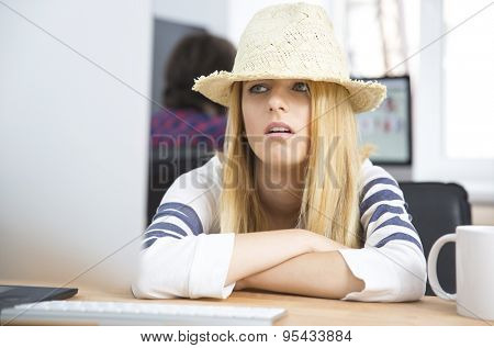 Tired young girl in hat sitting at the table and looking on monitor screen in office