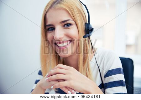 Happy young female operator in headset sitting at the table in office. Looking at camera