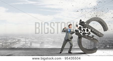 Businessman breaking stone euro symbol with karate punch