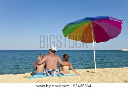 Grandfather hugging his grandson and granddaughter on a beach, looking to the see, back to the camera, colorful umbrella next to them.