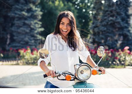 Laughing young woman on scooter looking at camera