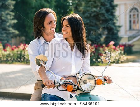 Happy couple flirting on scooter. Looking at each other