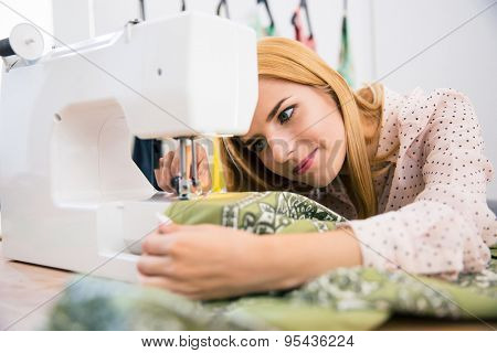 Pretty female tailor using sewing machine in laundry