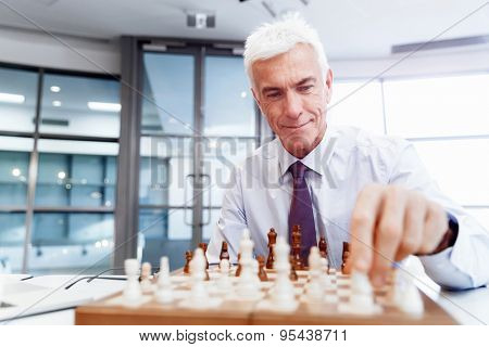 Businessman in office playing chess