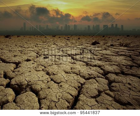 Global Warming and pollution theme with cracked land and the cityscape