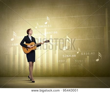 Cheerful businesswoman on financial background playing guitar