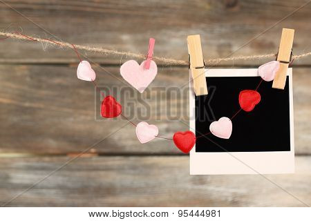 Bright hearts and photo paper hanging on rope on wooden background