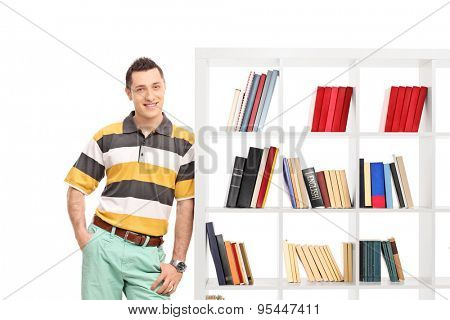 Casual young guy leaning against a bookshelf and looking at the camera isolated on white background