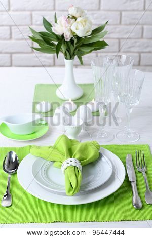 Beautiful table setting with flowers in vase on brick wall background