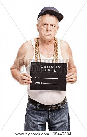 Vertical shot of a senior gangster in a hip hop outfit posing for a mug shot isolated on white background