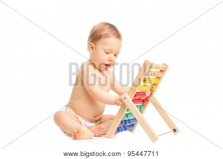 Studio shot of an adorable baby playing with an abacus seated on the floor isolated on white background
