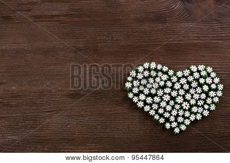 Sweet candies in heart shape on wooden background