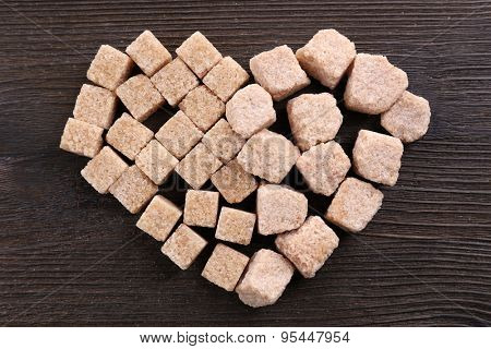 Sugar cubes in heart shape on wooden background