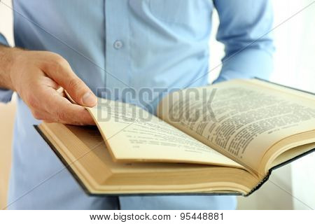 Young man reading book close up