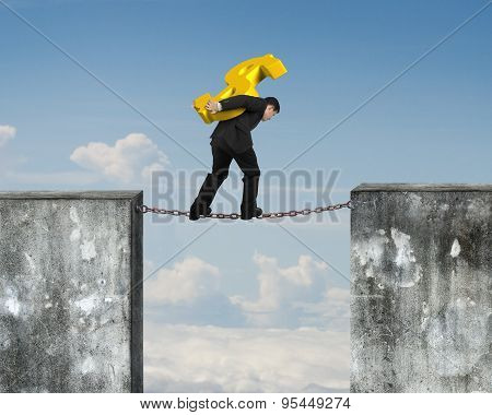 Businessman Carrying Golden Dollar Sign Balancing On Rusty Chain