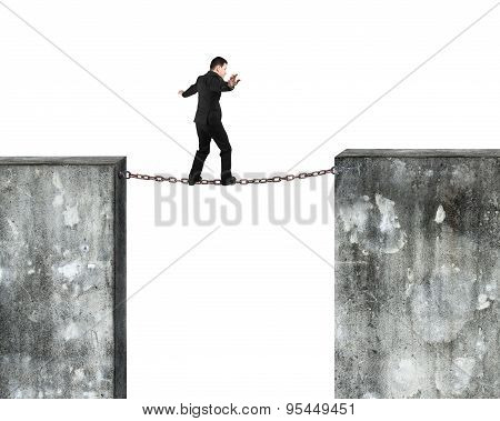 Businessman Balancing Rusty Chain Connected Concrete Walls