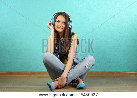 Young woman sitting on floor with headphones on turquoise wallpaper background