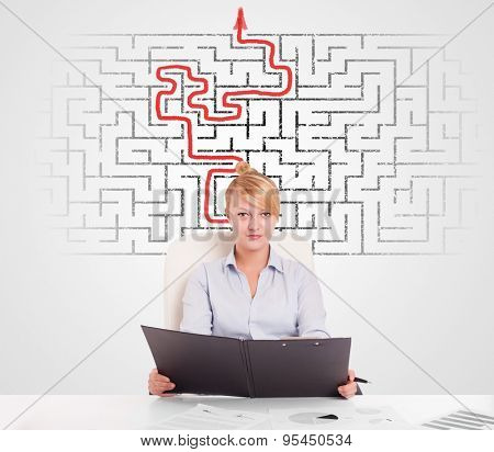 Business woman at desk with labyrinth in the background