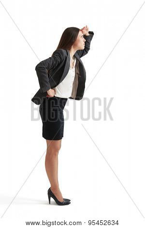 serious businesswoman in formal wear holding her hand near forehead and looking up. isolated on white background