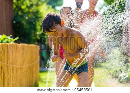 Family cooling down with sprinkler in garden, lots of water splashing around