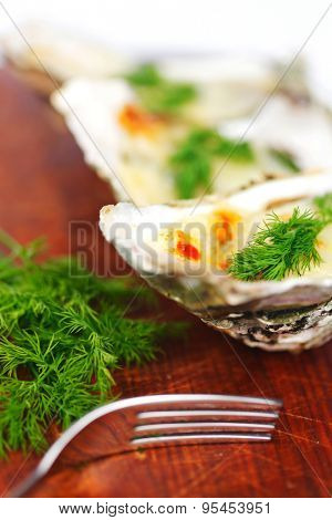 Oysters under cheese and dill on wooden table