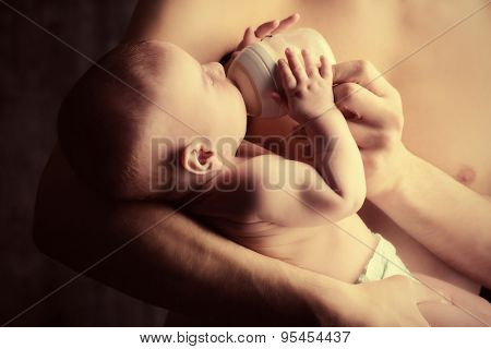 Caring father feeding his baby from a bottle. Healthy baby food and infant formula, milk. Studio shot over black background.