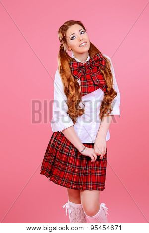 Cute smiling teen girl in school plaid skirt and white blouse posing over pink background. Anime style.